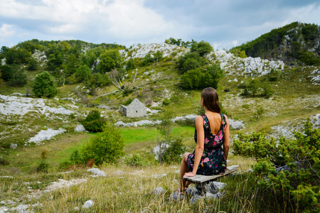 Beautiful young woman looking at the ruins of house. Montenegro, Europe.