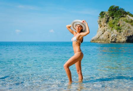 Sexy beautiful woman in white bikini and hat on Mediterranean sea coast Stockfoto