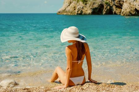 Sexy back of beautiful woman in white bikini with creative white sunglasses on Mediterranean sea coast. Montenegro, South Europe. Retro vintage toned image, film simulation. Stockfoto