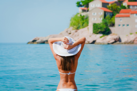 Sexy back beautiful woman at the sea coast with buildings of Mediterranean town on the background