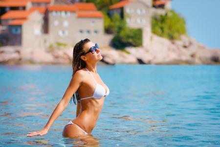 Sexy mujer hermosa en la costa del mar Mediterráneo con edificios antiguos. Foto de archivo