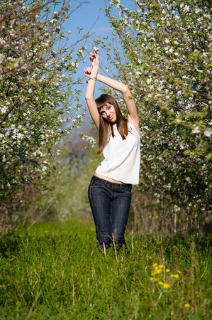 Young and beautiful woman (girl) is on the garden with apple trees in a blossom Stock fotó
