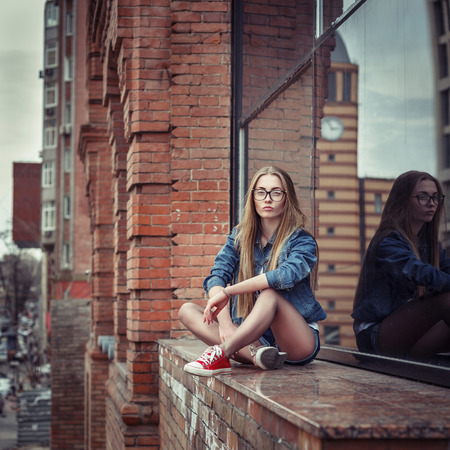 Outdoor lifestyle portrait of pretty young sitting girl, wearing in hipster swag grunge style urban background. Retro vintage toned image, film simulation. Stock Photo