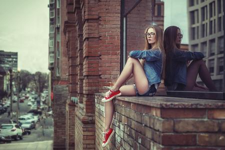 Retrato de estilo de vida al aire libre de una chica sentada bastante joven, vestida con fondo urbano de estilo grunge swag hipster. Imagen en tonos vintage retro, simulación de película. Foto de archivo