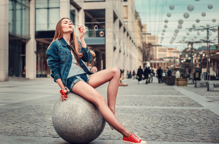 도시에서 거품을 부는 예쁜 소녀의 야외 라이프스타일 초상화, 힙스터 장식용 그루지 스타일 도시 배경을 입고 있습니다. 레트로 빈티지 톤 이미지, 필름 시뮬레이션. 스톡 콘텐츠