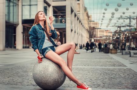 Portrait de mode de vie en plein air d'une jolie jeune fille soufflant des bulles dans la ville, portant un arrière-plan urbain de style grunge swag hipster. Image tonique rétro vintage, simulation de film. Banque d'images