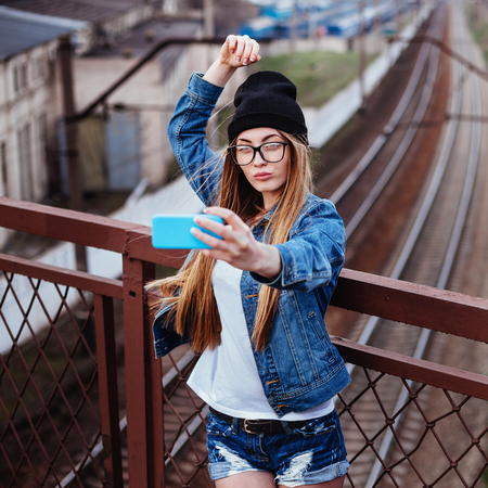 Outdoor lifestyle portrait of young sexy blonde hipster woman posing for selfie and laughing. Wearing jeans jacket, hipster black hat and glasses.