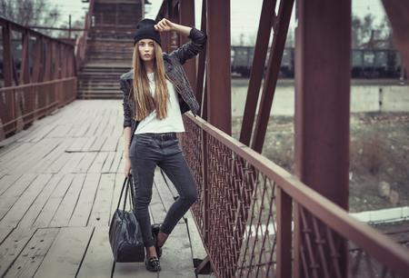 Zewnątrz portret całkiem młoda dziewczyna, ubrana w hipster łupem nieczysty styl tła miejskiego. Retro vintage stonowany obraz, symulacja filmu.