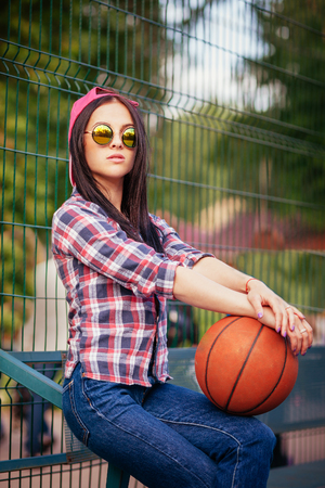 Outdoor lifestyle portrait of pretty young sitting girl, wearing in hipster swag grunge style with basketball in urban background. Retro vintage toned image, film simulation.