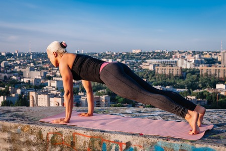 Portrait of blonde strong woman in sportwear doing workout stretching on the roof of skyscraper above the big city at early morning. Female sporty and sexy muscular body. Fitness concept. Stock Photo