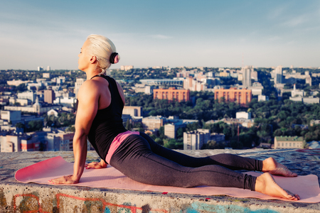 Portrait of beautiful blonde strong woman in sportwear doing workout on the roof of a skyscraper above the big city at early morning. Female sporty muscular body. Dawn and sunrise bright sunny light.