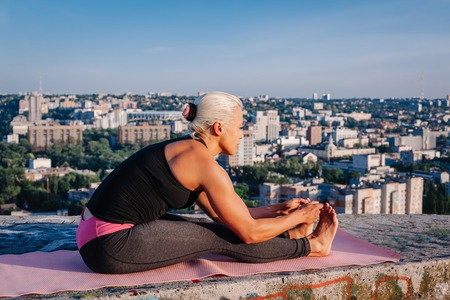 Portrait of blonde strong woman in sportwear doing workout stretching on the roof of skyscraper above the big city at early morning. Female sporty muscular body. Dawn and sunrise bright sunny light. 写真素材