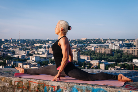 Portrait of blonde strong woman in sportwear doing workout stretching on the roof of skyscraper above the big city at early morning. Female sporty and muscular body. Fitness concept.