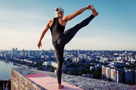 Portrait of beautiful blonde strong woman in sportwear doing workout stretching on the roof of a skyscraper above the big city at early morning. Female sporty muscular body. Dawn and sunrise bright sunny light. Stock Photo
