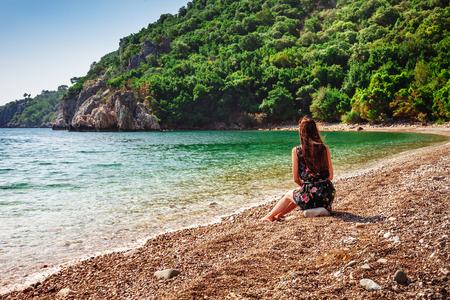 Portrait of beautiful tanned woman sitting at the sea coast. Hot summer day and bright sunny light. Panoramic view on sea shore near Kemer, Antalya, Turkey. Stockfoto