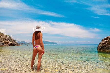 Sexy back of beautiful woman in bikini and creative hat on sea background. Sea coast near Kemer, Antalya, Turkey