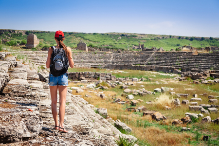 Pretty tourist woman with backpack at the ruins of ancient city of Perge near Antalya Turkey Stock Photo