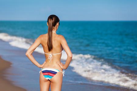 Parte posteriore sexy di una bella donna in bikini sullo sfondo del mare. Glutei sexy. Immagine dai toni vintage retrò, simulazione di film. Archivio Fotografico