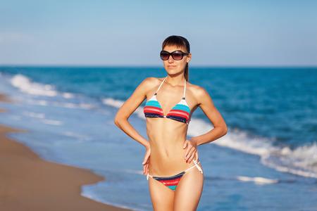 Mode outdoor portret jonge dame met plezier en poseren in gestreepte bikini en zonnebril op zee achtergrond. Zonsondergang licht. Stockfoto