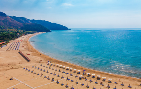 Beach and sea landscape with Sperlonga, Lazio, Italy. Scenic resort town village with nice sand beach and clear blue water in picturesque bay. Famous tourist destination Riviera de Ulisse Banco de Imagens
