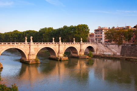 Panorama cityscape from the ancient embankment Tiber in Roma at sunset. Near of bridge and castle of Angels. Saint Angelo castle and bridge is famous tourist destination in Italy