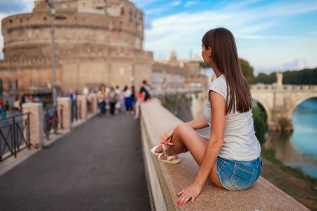 Giovane donna turistica seduta sull'antico argine del Tevere a Roma al tramonto. Vicino a ponte e castello degli Angeli. Il castello e il ponte di Sant'Angelo sono una famosa destinazione turistica in Italia