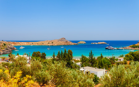 Sea skyview landscape photo Lindos bay and castle on Rhodes island, Dodecanese, Greece. Panorama with ancient castle and clear blue water. Famous tourist destination in South Europe 免版税图像