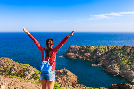 Tourist woman with backpack on Cap de Creus, natural park. Eastern point of Spain, Girona province, Catalonia. Famous tourist destination in Costa Brava. Sunny summer day with blue sky and clouds Stock Photo