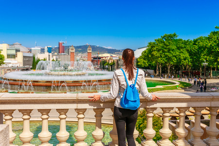 Tourist woman see on skyline of beautiful Barcelona from the Montjuic in a clear blue sky and sunny day. Famous tourist destination Catalonia, Spain Banco de Imagens