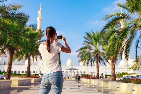 Young tourist woman shooting on mobile phone Sheikh Zayed great white mosque in Abu Dhabi, United Arab Emirates, Persian gulf. UAE is famous tourism destination Фото со стока