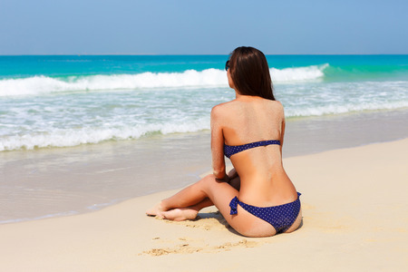 Sexy back of a beautiful unrecognizable woman relaxing and sunbathing in bikini on sea background and palm. Sexy buttocks. Beach in Dubai, UAE famous tourist destination