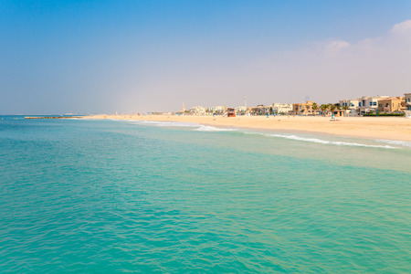 Panoramic view on nice Jumeirah beach in Dubai, UAE. United Arab Emirates famous tourist destination. Clear blue water Persian gulf, Indian Ocean