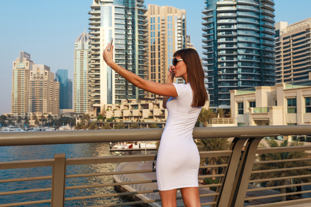 Happy beautiful tourist woman in fashionable summer white dress and sunglasses shooting mobile phone in Dubai marina in United Arab Emirates. Luxury and comfortable tourism season in UAE. Stok Fotoğraf