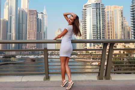 Happy beautiful tourist woman in fashionable summer white dress walking and enjoying in Dubai marina in United Arab Emirates. Luxury and comfortable tourism season in UAE. Warm summer day.