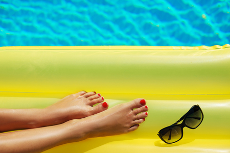 Portrait of beautiful tanned woman relaxing in swimming pool. Sunglasses and inflatable matress. Legs close up. Creative gel polish red pedicure and manicure. Hot summer day, bright sunny light.