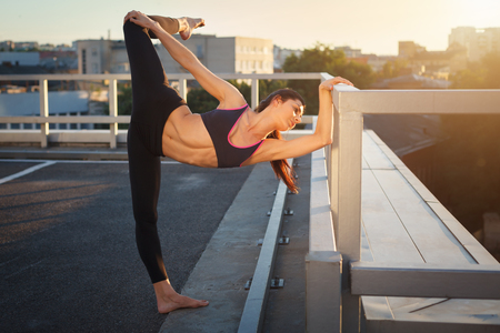 Portrait of beautiful strong woman in sportwear doing workout yoga exercise and stretching on urban background. Female sporty muscular body. Sunset bright light. 版權商用圖片