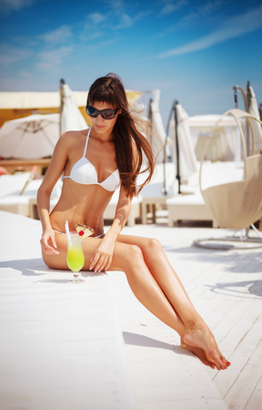 Portrait of beautiful tanned exotic woman relaxing near swimming pool in white swimwear with yellow cocktail. Manicure and pedicure. Hot summer day and bright sunny light. Stock Photo