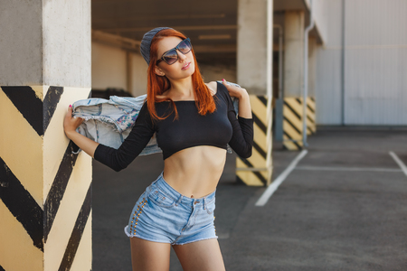Outdoor lifestyle fashion portrait of pretty young girl, wearing in hipster swag grunge style urban background. Red hair.