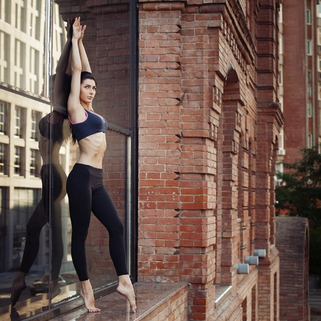 Portrait of beautiful strong woman in sportwear doing workout yoga exercise and stretching on urban background. Female sporty muscular body.