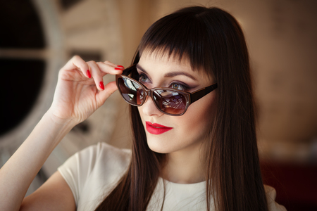 Closeup fashion beautiful woman portrait wearing sunglasses with red gel polish manicure. Make up model. Фото со стока - 122957077