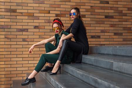 Beautiful fashion women posing. Trendy lifestyle urban portrait on city background. Girls wearing in style clothes and accessories Stockfoto