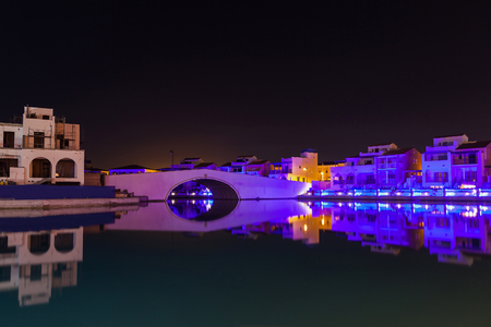Night panorama from coast in Limassol, Cyprus island, Mediterranean Sea. Colourful bridge and buildings with reflection in water surface Archivio Fotografico
