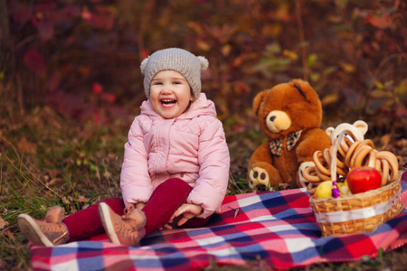 Portrait of beautiful happy child sitting on plaid with autumn colorful leaves background. Picnic basket with apples and bagels, toy bears. Funny girl outdoors in fall park.