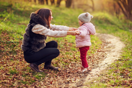 Young mother playing with daughter on autumn forest background. Family walking in park. Bright back light.