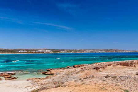 Beautiful landscape sand beach near of Nissi beach and Cavo Greco in Ayia Napa, Cyprus island, Mediterranean Sea. Amazing blue green sea and sunny day.
