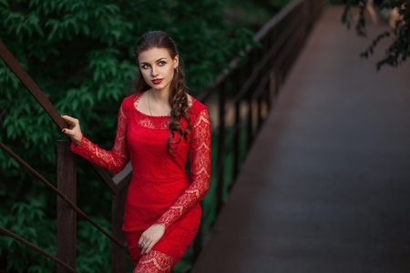 Beautiful fashion woman posing in red dress with creative hairstyle. Trendy urban portrait on green background. Stock fotó