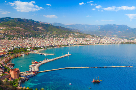 Landscape of Alanya with marina and Kizil Kule red tower in Antalya district, Turkey, Asia. Famous tourist destination with high mountains. Summer bright day and sea shore Stock fotó