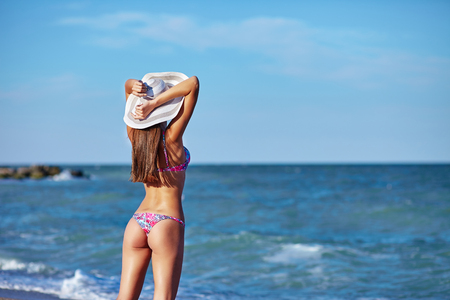 Sexy back of a beautiful woman in bikini on sea background. Sexy buttocks. Exotic country travel and rest concept. Stock fotó