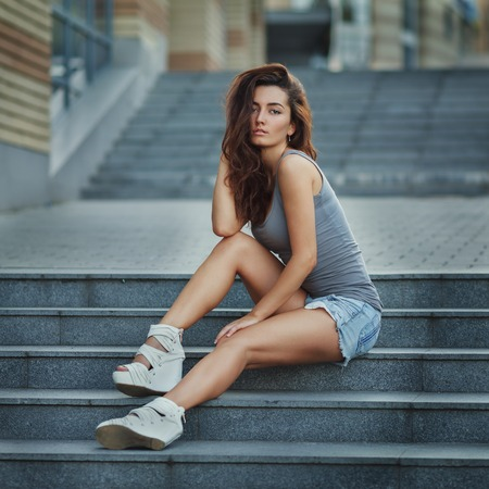 Outdoor lifestyle portrait of pretty young girl posing on stairway, wearing in hipster urban style on urban background.