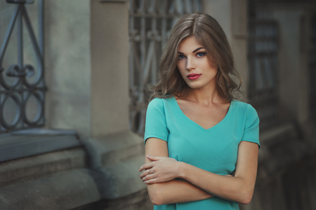 Outdoor lifestyle portrait of pretty young girl, wearing in blue dress on urban background. Creative color toned image. Stock fotó
